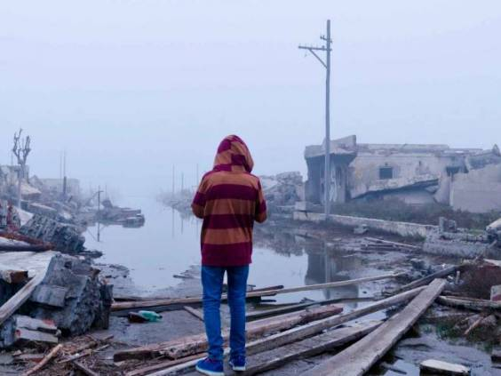 boy watching the flood in Epecuen, Buenos Aires, Argentina. Climate change. Ruins of flooded city.