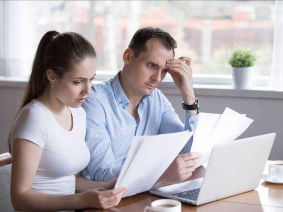 Serious couple looking at sheets of paper, looking concerned at kitchen table