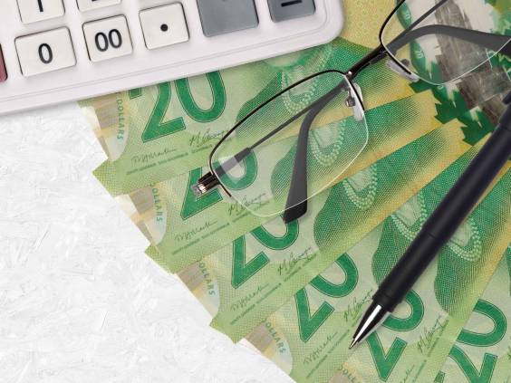 20 Canadian dollars bills fan and calculator with glasses and pen. Business loan or tax payment season concept