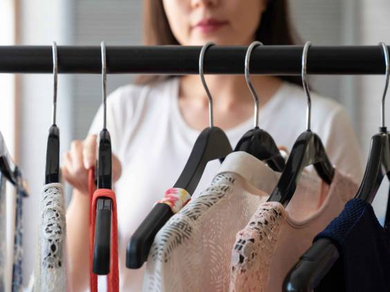 Woman going through clothing on a rack and picking items.