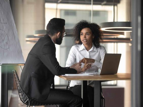 Woman talking seriously to man while they sit at an office desk.