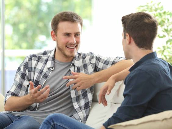 Two friends talking sitting in a couch in the living room with a window in the background at home