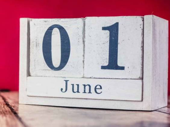 June 1st. Day 1 of month, calendar on business office table, workplace with vivid maroon red background. Summer time