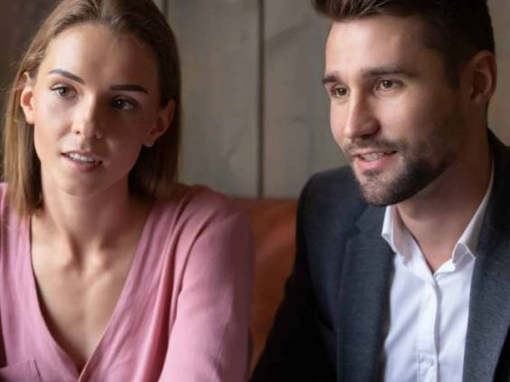 Focused Caucasian husband and wife talk discuss buying house with female real estate agent in coffeehouse, concentrated couple meeting with wedding planner or financial consultant in cafe