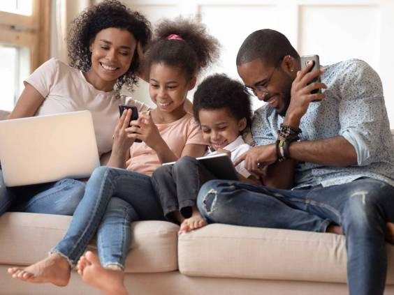 Family sits together on couch looking at devices, smiling.