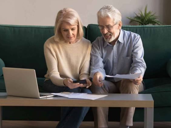 Smiling contemporary senior couple manage domestic expenditures at home