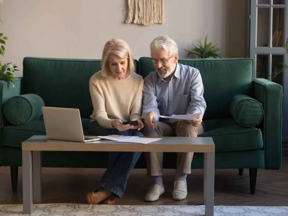 Smiling contemporary senior couple spouses use laptop and manage bills