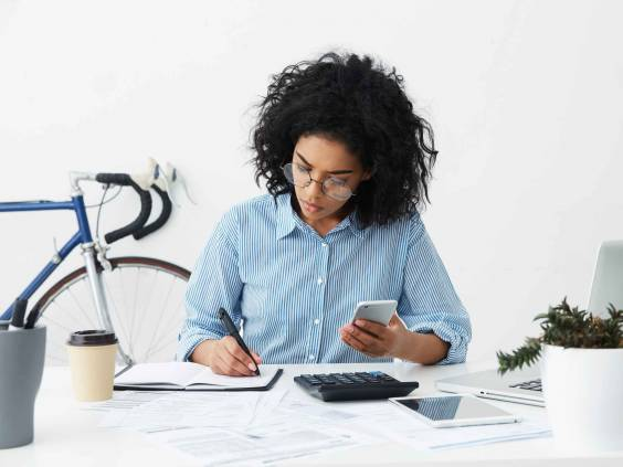 Concentrated focused Afro American woman holding phone in one hand and making notes with pen in other