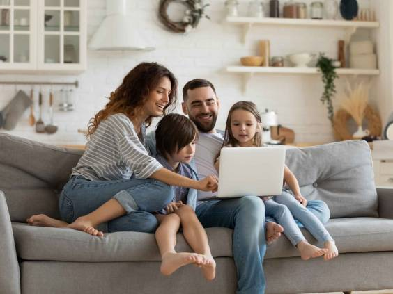 Happy young family with little kids sit on sofa using laptop