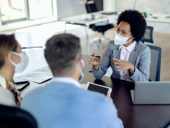Happy black financial advisor communicating with a couple on a meeting in the office. All of them are wearing protective face masks due to COVID-19 pandemic.