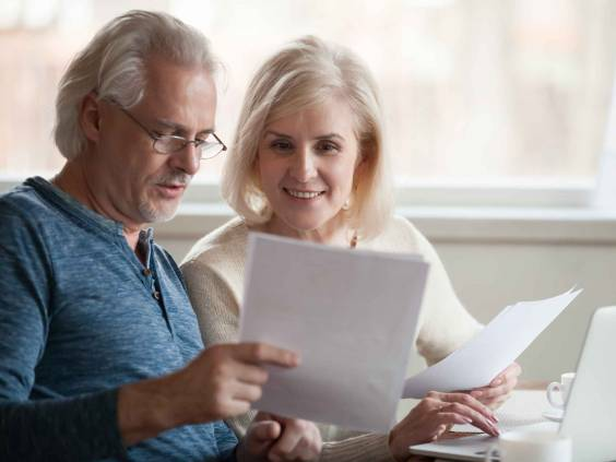 Happy old middle aged couple reading good news in document