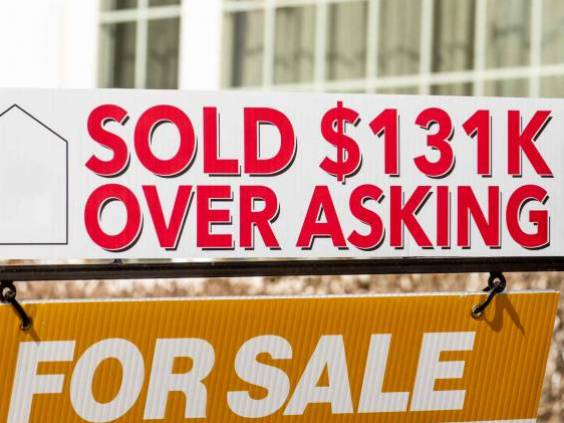 A real estate For Sales sign with a Sold $131K Over Asking notice suggesting a hot or overheated housing market
