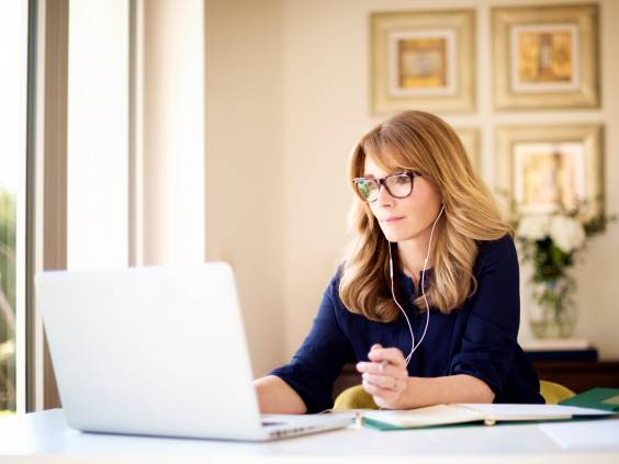 Woman sitting at desk at home, looking at something on computer, wearing headphones.