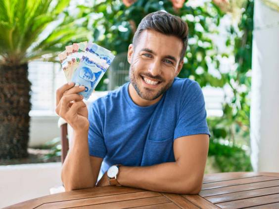 Young hispanic man smiling happy holding Canadian dollars banknotes at the terrace.