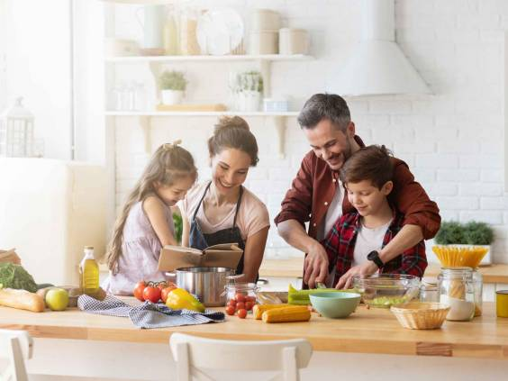 Happy family cooking together in kitchen.