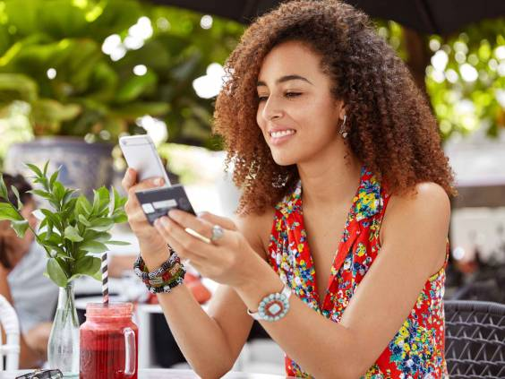 Young woman sits at cafe with phone and credit card in her hands.