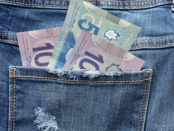 A close up image of Canadian money in a pants pocket.