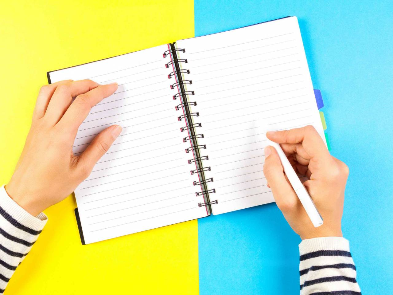 Woman hand writing in notebook over blue and yellow background.