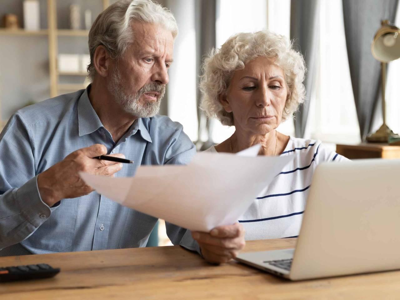 elderly couple worrying over finances