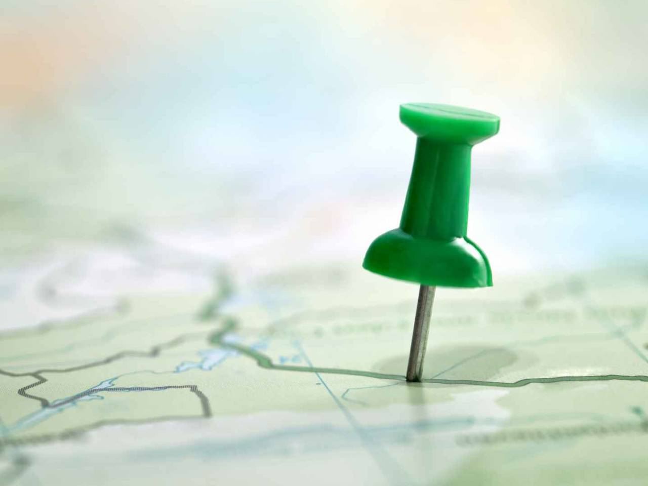 Pushpin showing the location of a destination point on a green map