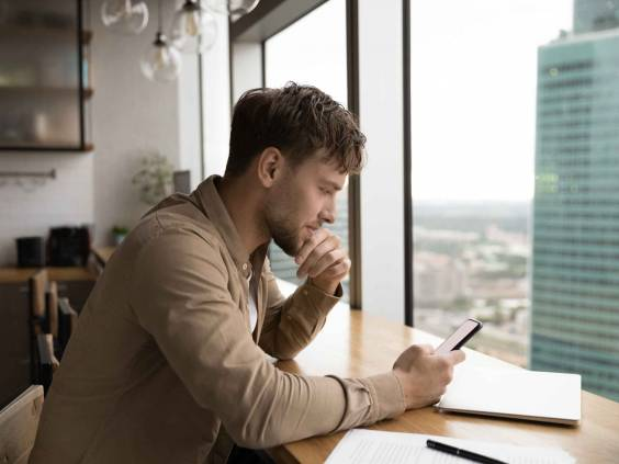 Information to think about. Pensive male look at cell ponder on job offer received by email. Young businessman sit by large window at modern kitchen, read important message on phone screen