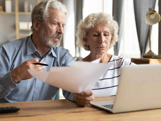 Stressed elderly married couple paying taxes
