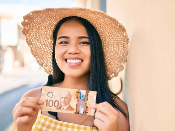 Young asian girl smiling happy at the city holding canadian dollars banknotes