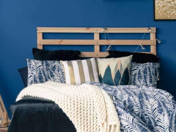 Stylish bedroom interior with dark blue wall