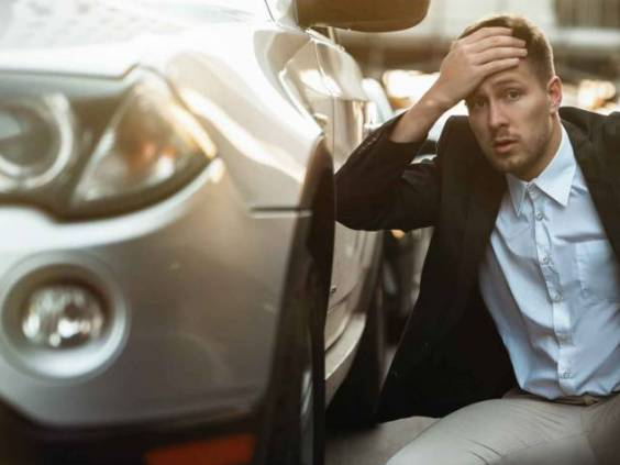young handsome businessman looks nervous just had car crush in the middle of the road , unexpectable vehicle trouble