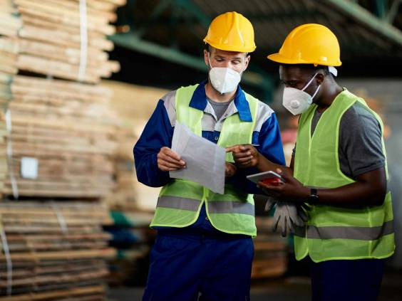 Two manual workers with face masks going though checklist while working in timber warehouse.