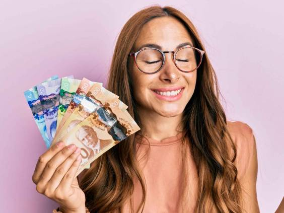 Young brunette woman holding canadian dollars screaming proud, celebrating victory and success very excited with raised arm