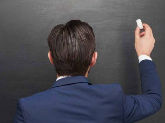 Photo of young businessman on blank chalkboard background.