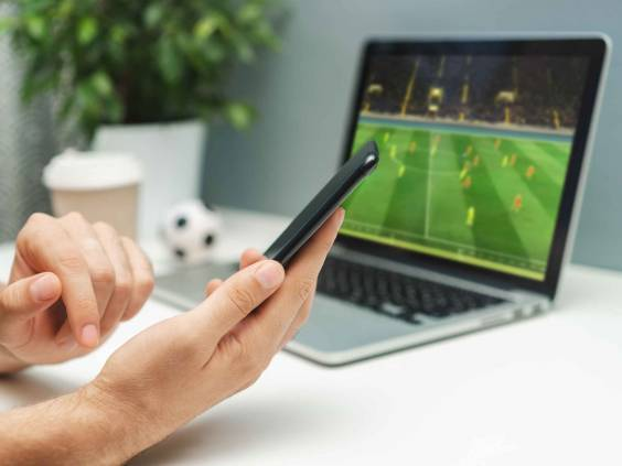 Close up cropped shot of male hand holding smartphone. Man watching soccer play live broadcast online on his laptop and making bets on his favourite team using mobile application.