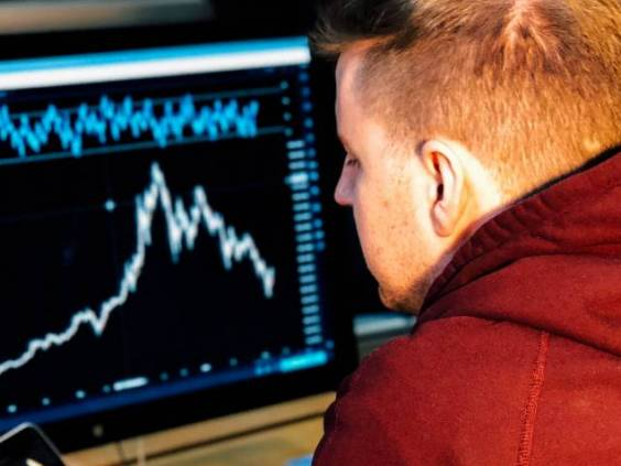 Man investing and checking stocks on computer