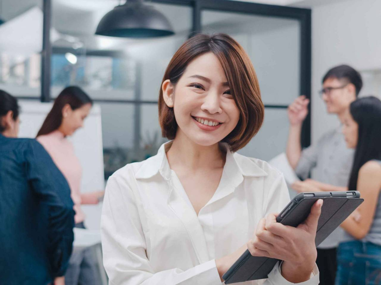 Business woman smiling and holding a tablet in the office