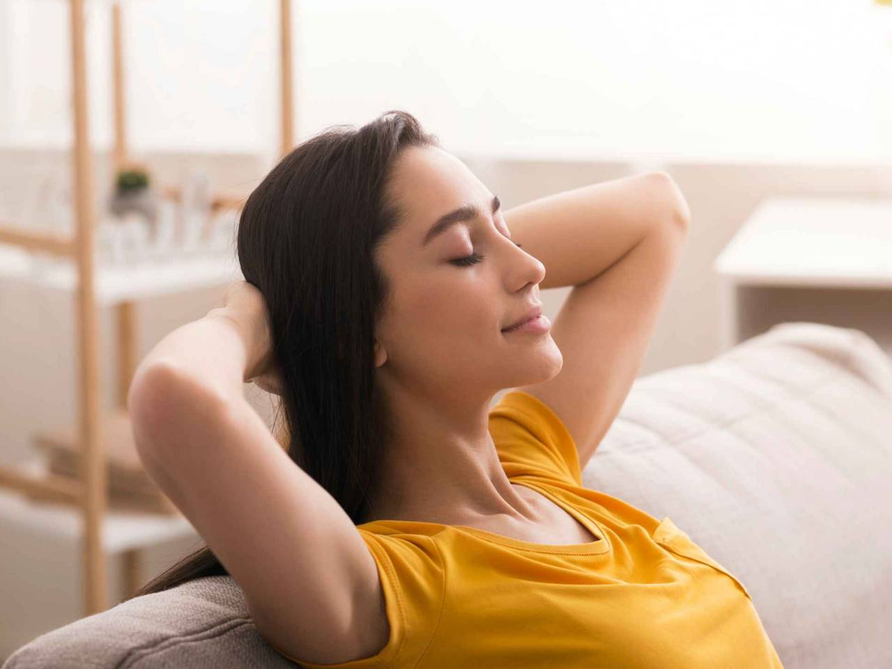 Keep calm and stay home. Peaceful young woman relaxing on sofa in living room
