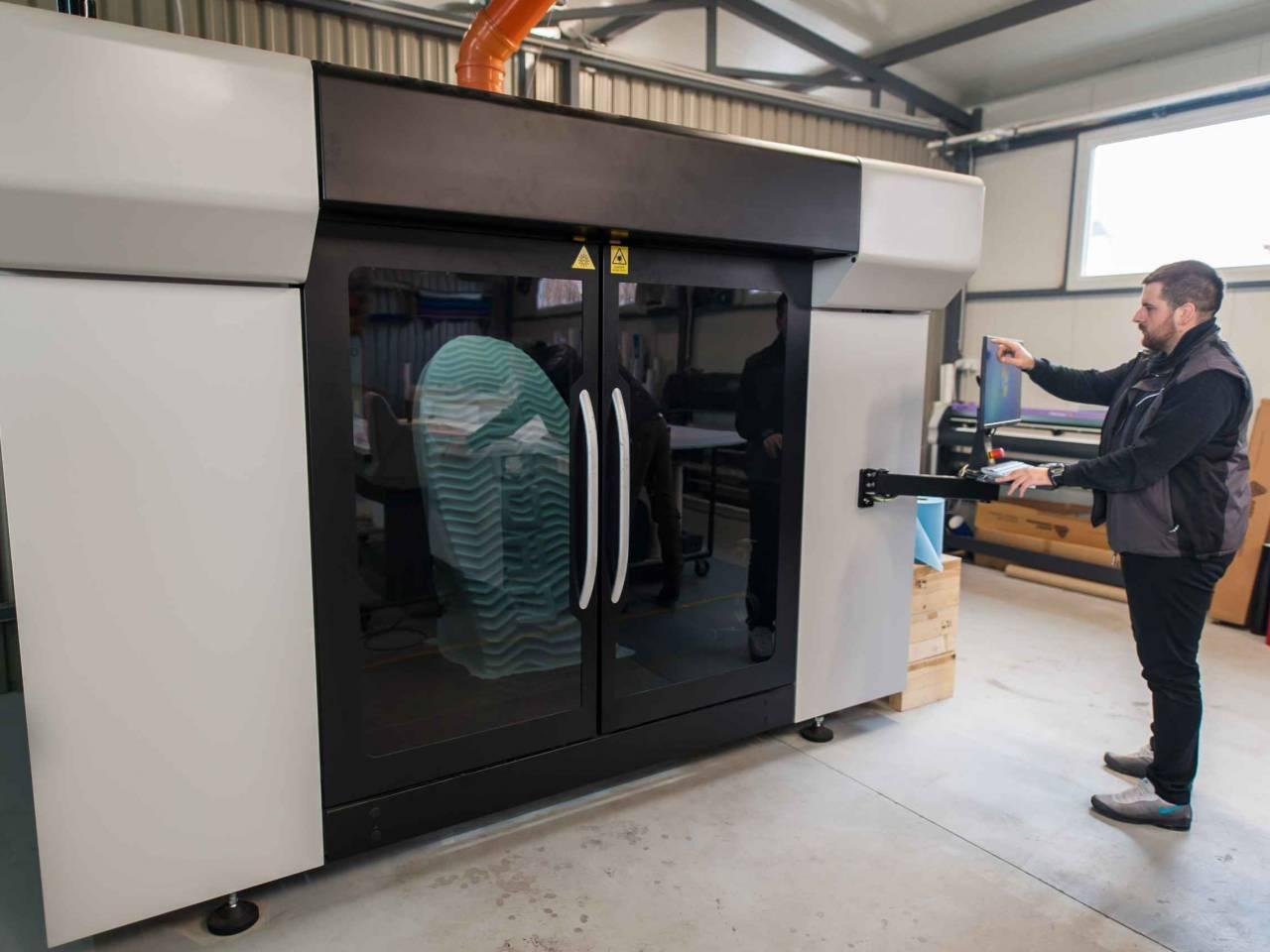Printshop worker printmaker technician works on large modern 3d printer machine with computer control