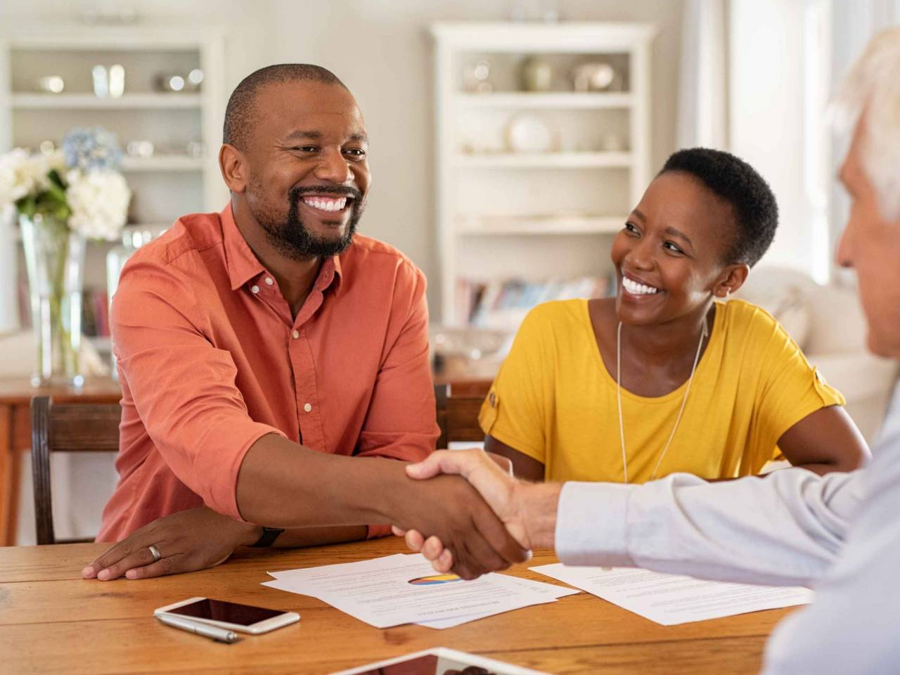 Mature black husband shaking hands with senior agent on taking loan.