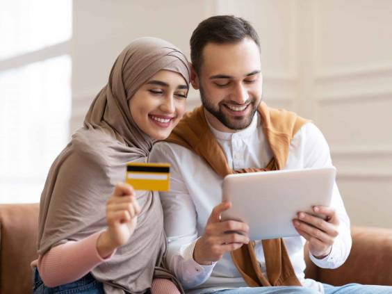 Online Shopping. Happy Muslim Couple Using Digital Tablet And Credit Card Buying And Purchasing Things Sitting On Sofa At Home. Joyful Customers, Modern Shopping And Sales Concept