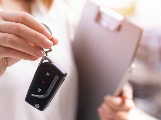 Woman holding a set of keys for a car with a clipboard in her hand