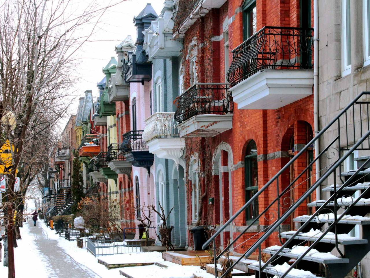 Beautiful houses of old historical Montreal neighborhood Plateau Mont Royal in winter season, bright painted doors.