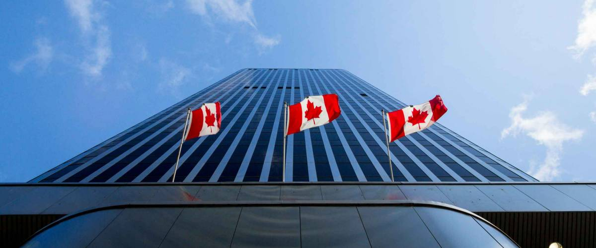 Three Canadian flags in front of a business building in Ottawa