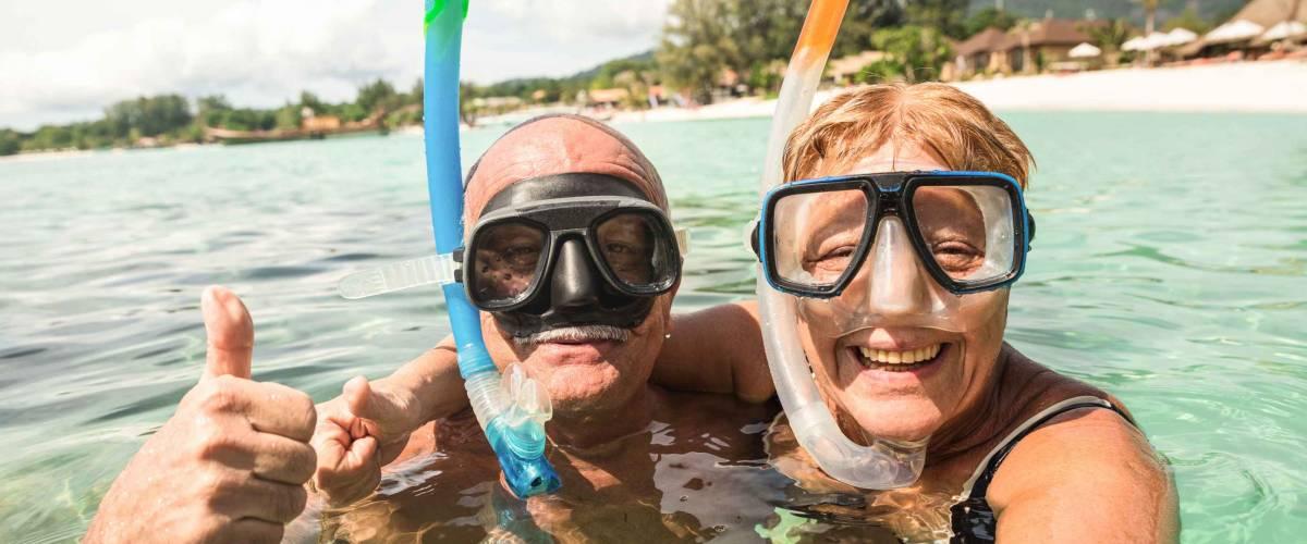 Senior happy couple taking selfie in tropical sea excursion