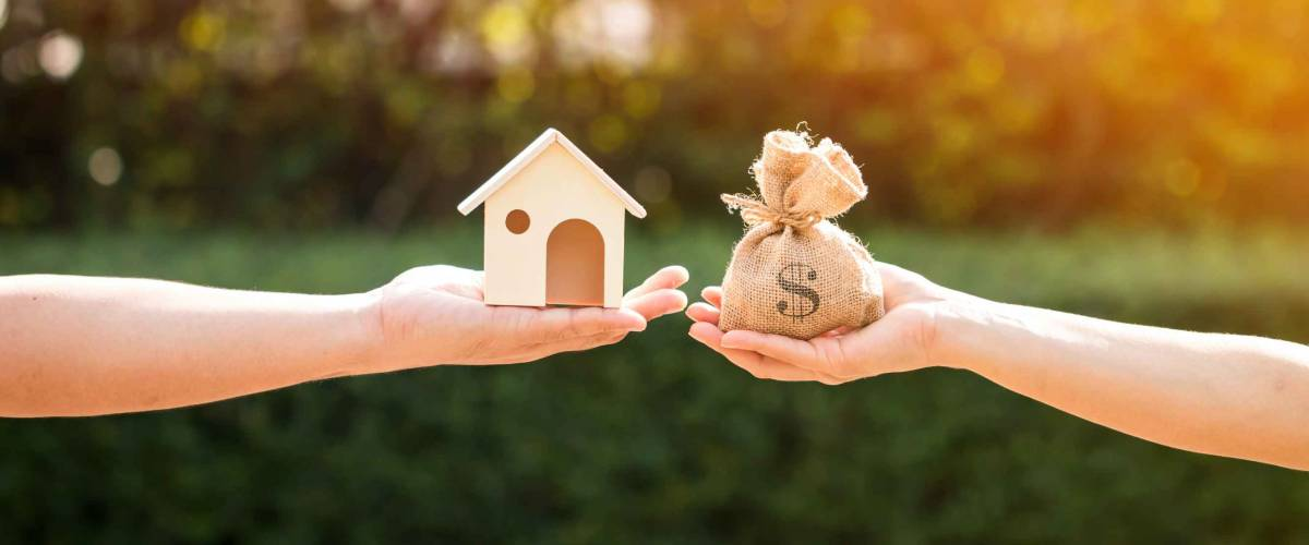 A man and a women hand holding a money bag and a model home