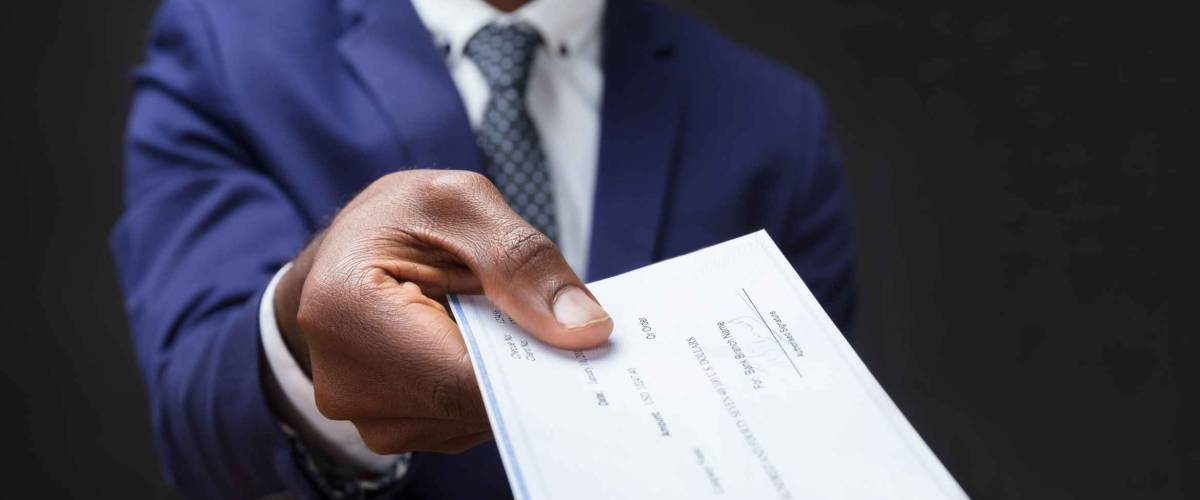Close-up Of A Businessman's Hand Giving Cheque Over Wooden Desk