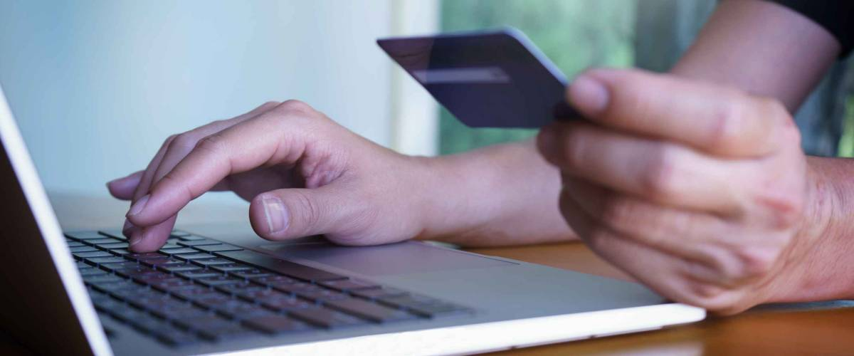 Man's hands holding credit card and typing on the keyboard of laptop, onine shopping, online payment.