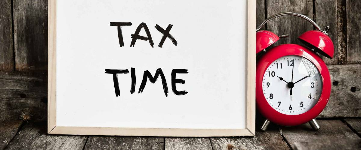 Tax time message note on white board with red retro clock on wooden background.
