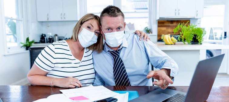 Stressed couple with masks in self-isolation over home finances