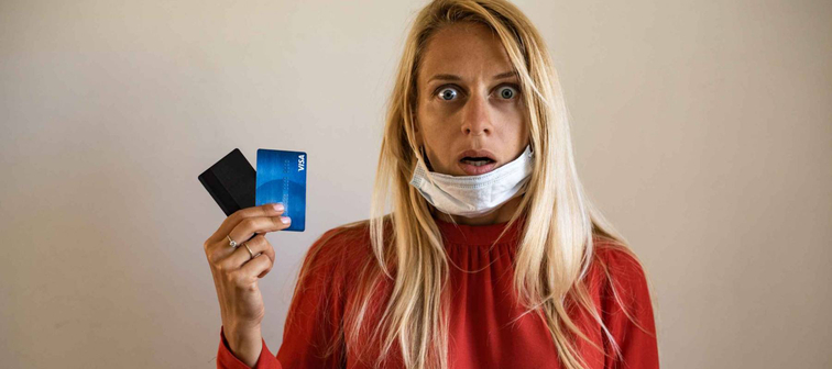 A blond girl wears a protective medical mask, holds a credit card, on a beige background. The concept of quarantine, coronavirus, shopping. shock, credit, no have money, work after quarantine