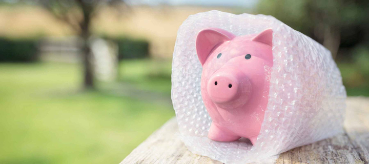Piggy bank wrapped in bubble wrap, protecting your savings and money